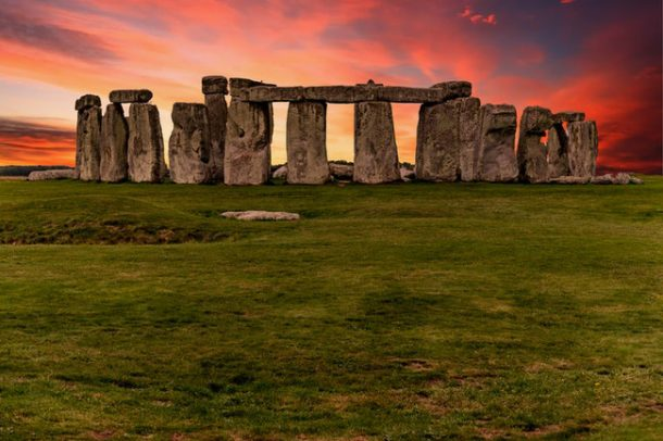 The massive rock towers lined up at Stonehenge, with a green grass foreground and a beautiful sky containing pink and orange tinted clouds as the background.