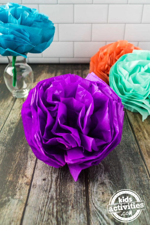One Mexcian tissue paper flower displayed on a vase and other pom poms flowers are displayed in front of the vase