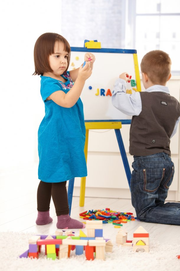 Letter R - kindergarten boy and girl with hands-on learning through letters on an easel