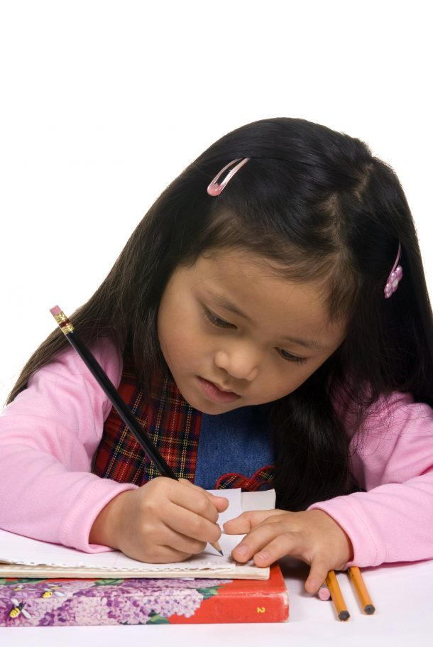 Preschool girl practicing formation of the letter B handwriting