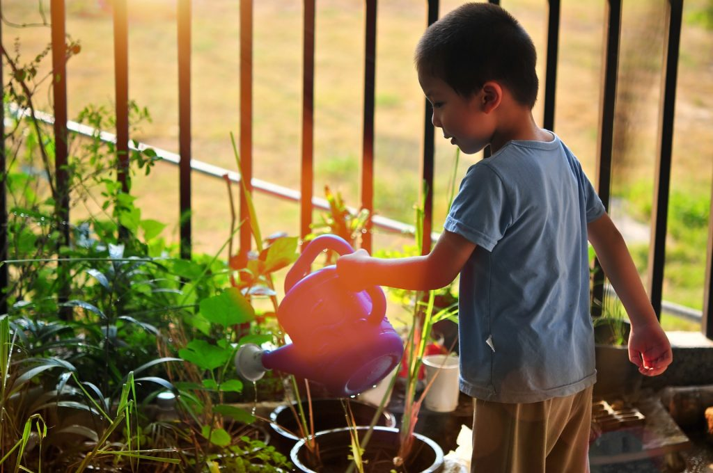Child with watering can and garden on a patio