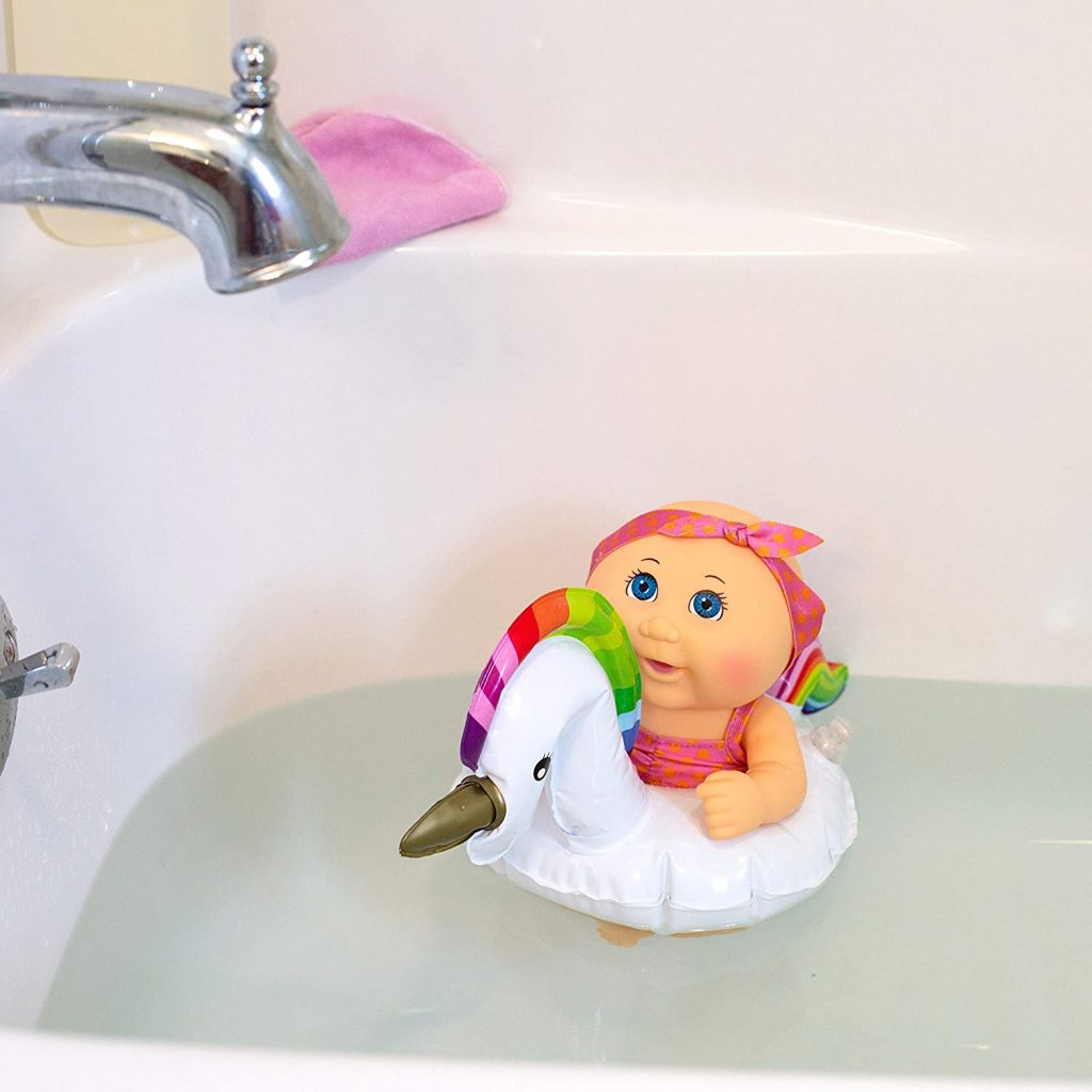 swimming doll in unicorn floatie in the bath tub with water