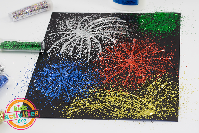 fireworks art using glitter and glue - Kids Activities Blog - in process showing glitter of 4 colors on top of glue on black paper