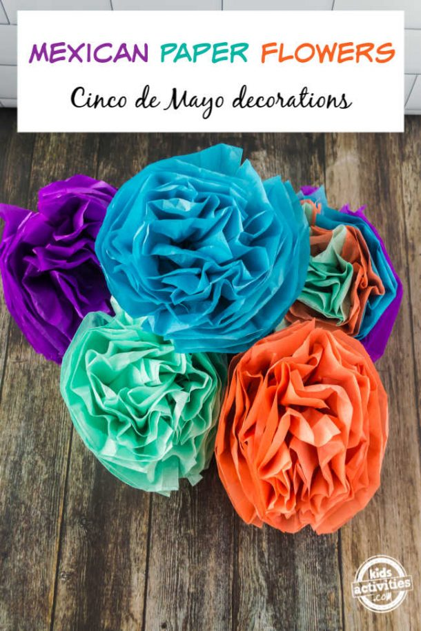 A bunch of colorful tissue paper flowers arranged on a wooden background making beautiful Mexican paper flowers to celebrate Cinco de Mayo along with the piñata