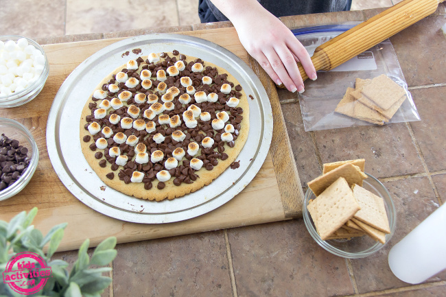 a s'mores pizza with graham crackers being crushed to sprinkle over the top