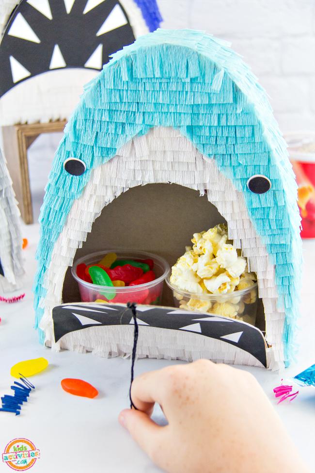a cereal box shark filled with popcorn and candy