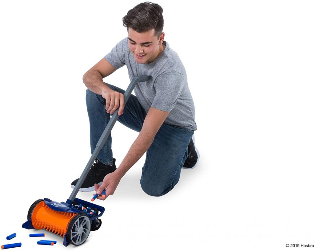 The boy in a gray t-shirt and jeans is now getting the nerf darts out of the basket on the back of the nerf vacuum.