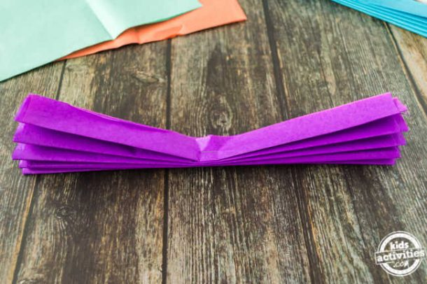 tissue paper folded in accordian style and stapled in the center for making mexican paper flowers for cinco de mayo crafts