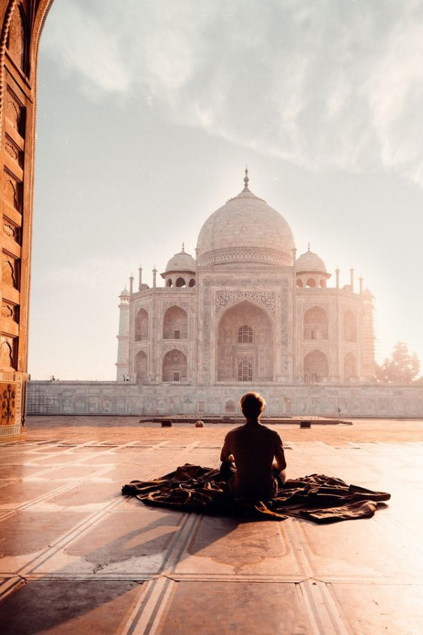 A person sitting on a blanket on the floor in front of the Taj Mahal in India, looking at the beautiful white monument as the sun hits him from the side.