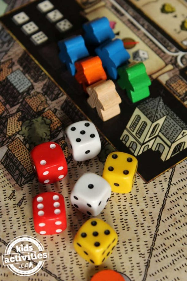 A bunch of colorful die and playing pieces scattered on a board game surface.