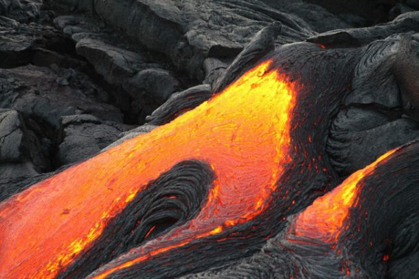 Molten orange and yellow lava moving around the black volcano ash and rock at Hawaii Volcanoes Park.