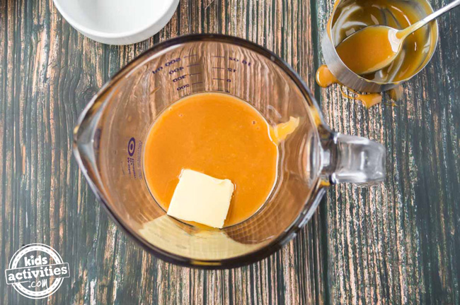 A pat of butter sitting in a bowl with butterscotch syrup.