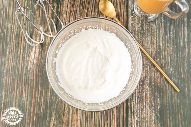 A bowl of heavy cream that has been whipped using a hand mixer.