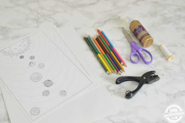 Supplies for making hanging solar system mobile which includes solar system coloring pages, cardstoc, colored pencils, thread, glue, scissors and a hole punch