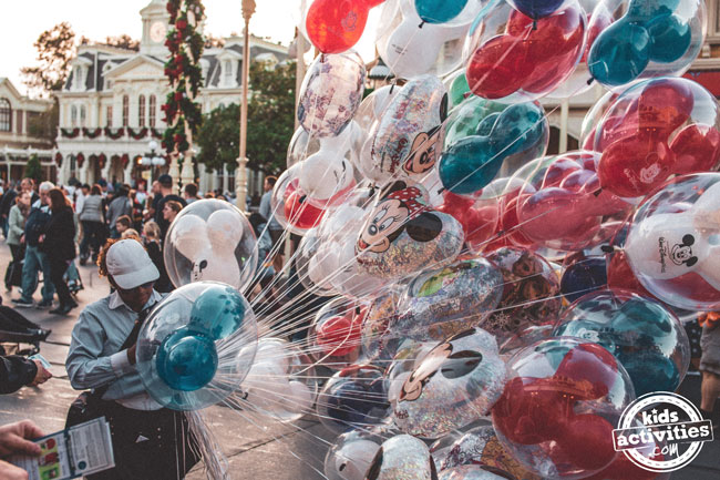 A female Disney employee selling mickey and minnie balloons on the street at Disneyland.