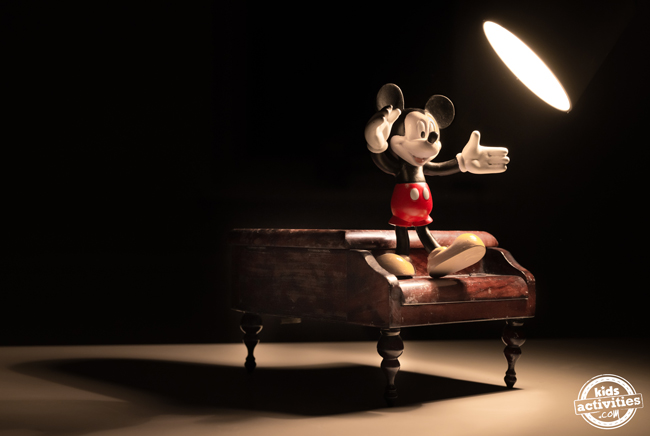 A Mickey mouse figurine standing on top of a piano with a spotlight on him.