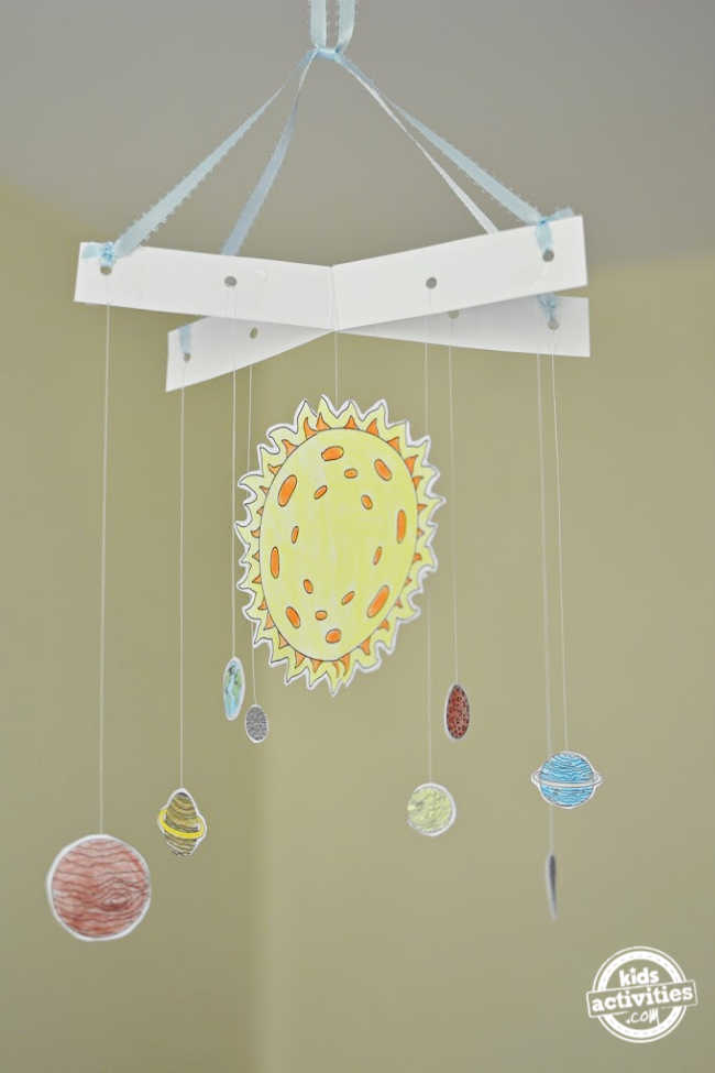 With sun in the center and other planets are hanged from the cardstock hanging frame as a solar system hanging mobile