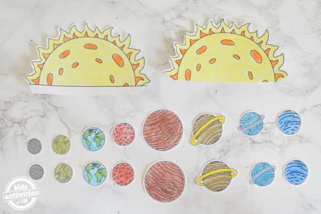 Sun and the planets are cut from the solar system coloring pages to make solar system for kids