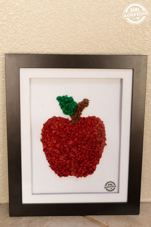 A black frame containing a piece of white cardstock with a red tissue paper apple on the paper.