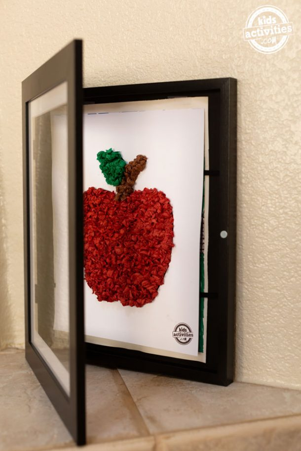 A black, front-loading frame halfway open to reveal a piece of white cardstock with a tissue paper apple on it.