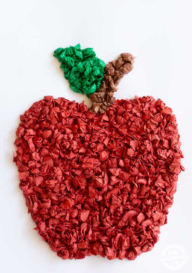 Red, green, and brown tissue paper apple on white cardstock.