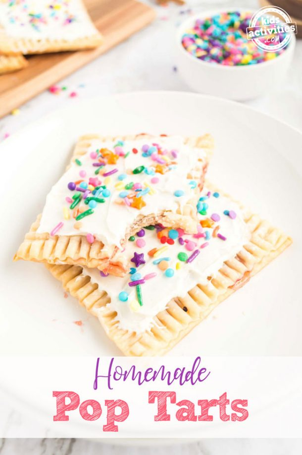 Two homemade pop tarts topped with white frosting and colorful sprinkles sitting on a white plate.