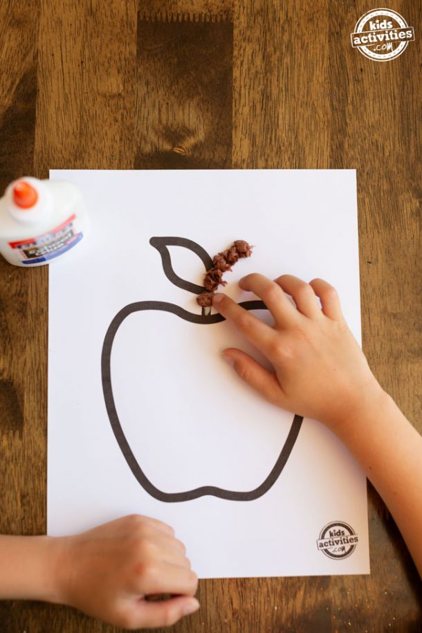 Apple printable on white cardstock with a boy's hand placing a ball of brown tissue paper on the apple's stem. Glue bottle sitting on the left side of the frame.