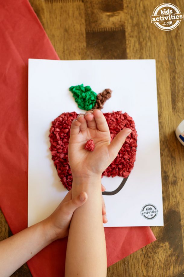 A boy holding a rolled up ball of red tissue paper above an in-progress tissue paper apple craft.