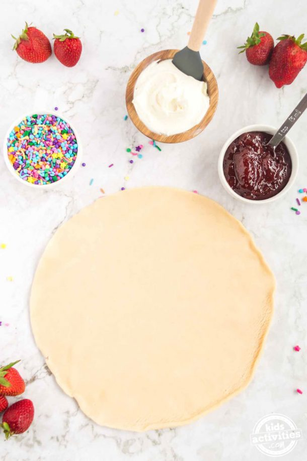 The four ingredients to make homemade pop tarts: pie crust rolled out, sprinkles, strawberry jam and vanilla frosting.