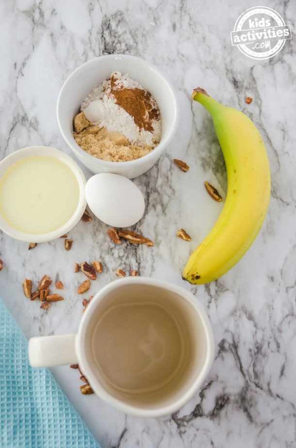 All the ingredients you need to make a banana nut mug cake, including a banana, an egg, nuts -- all sitting on a white and gray kitchen counter with a blue towel nearby.