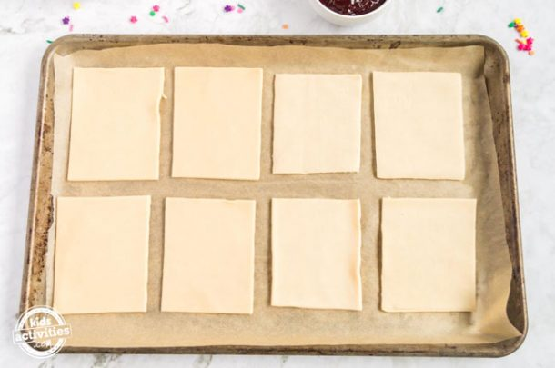 Eight rectangles of pie crust assembled on parchment paper on a baking sheet.