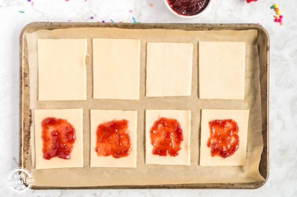 Eight rectangles of pie crust assembled on parchment paper on a baking sheet. Four of the pieces have strawberry jam on them.