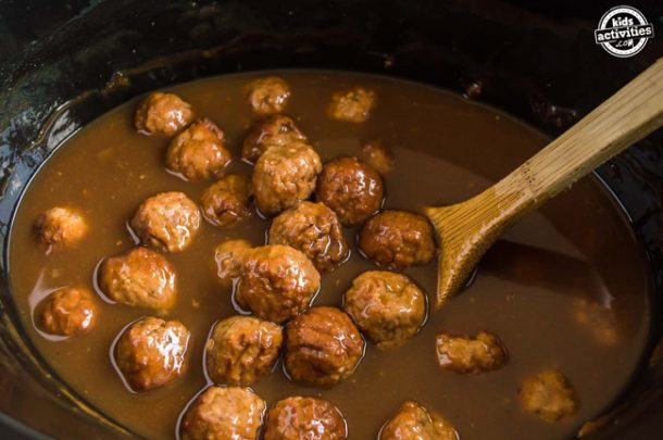 Slow Cooker Swedish Meatball Recipe Instructions step 4 - A slow cooker filled with Swedish meatballs and sauce and a wooden spoon.