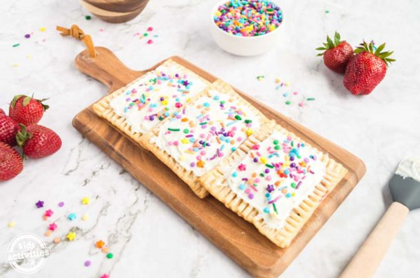 A wooden board containing three ready-to-eat homemade pop tarts, all covered in vanilla frosting and sprinkles.