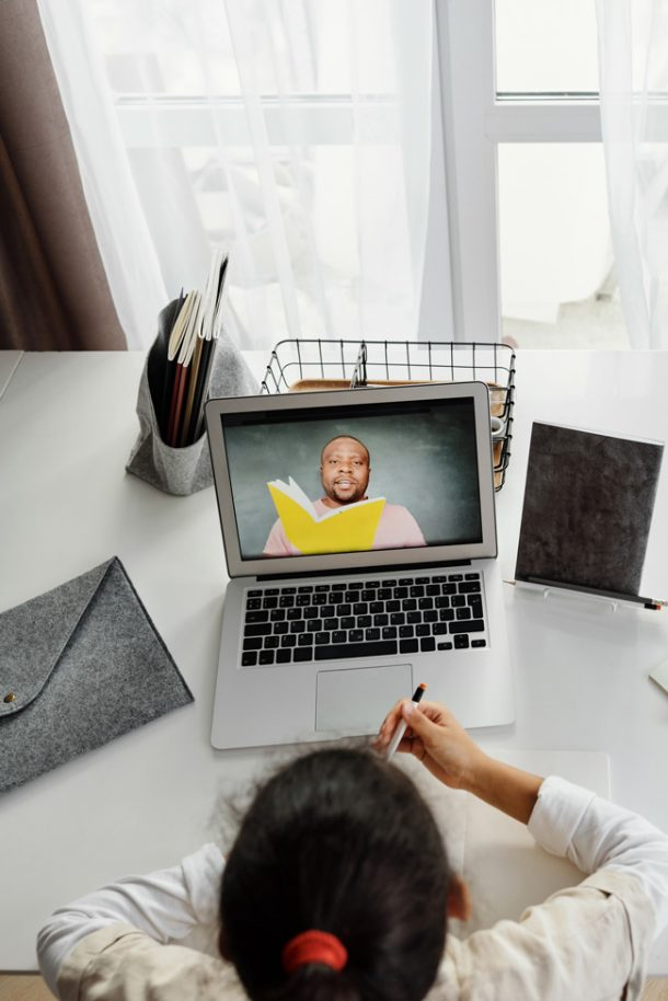 A girl sitting in front of a laptop computer. On the screen is a man reading a yellow book.