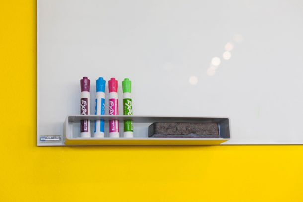 A whiteboard with four dry erase markers and an eraser.