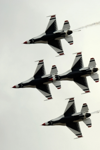 Four Air Force Thunderbirds piloted by Alliance fly against a backdrop of gray sky.