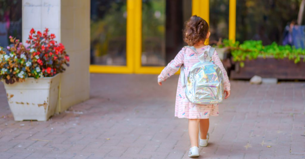 Child going to school in a pink dress and holo backpack who has a good routine and structure in their life to help deal with ADHD.