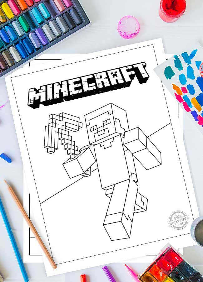 A Minecraft coloring sheet printed on white paper with Steve holding a diamond axe. Art supplies surround the printable.