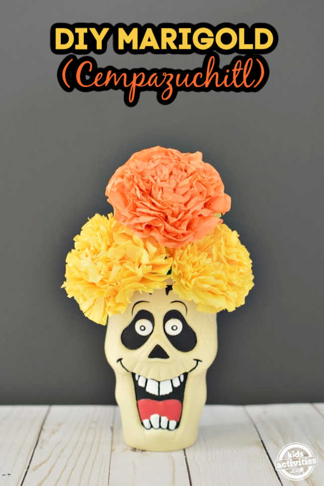 Tissue paper marigold flowers arranged on a skull in a black background for day of the dead cempazuchitl