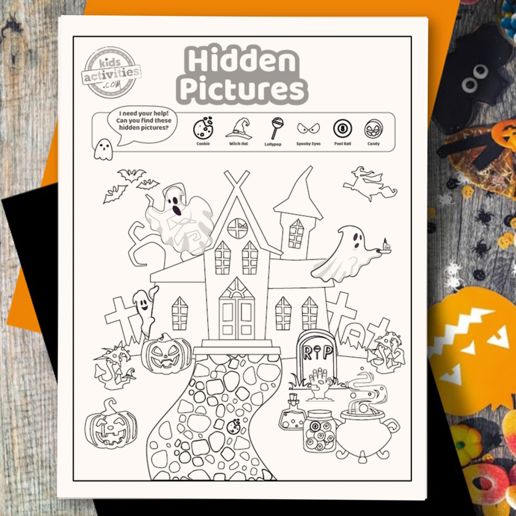 Halloween hidden picture coloring page activity on a wood surface surrounded by Halloween art and craft supplies