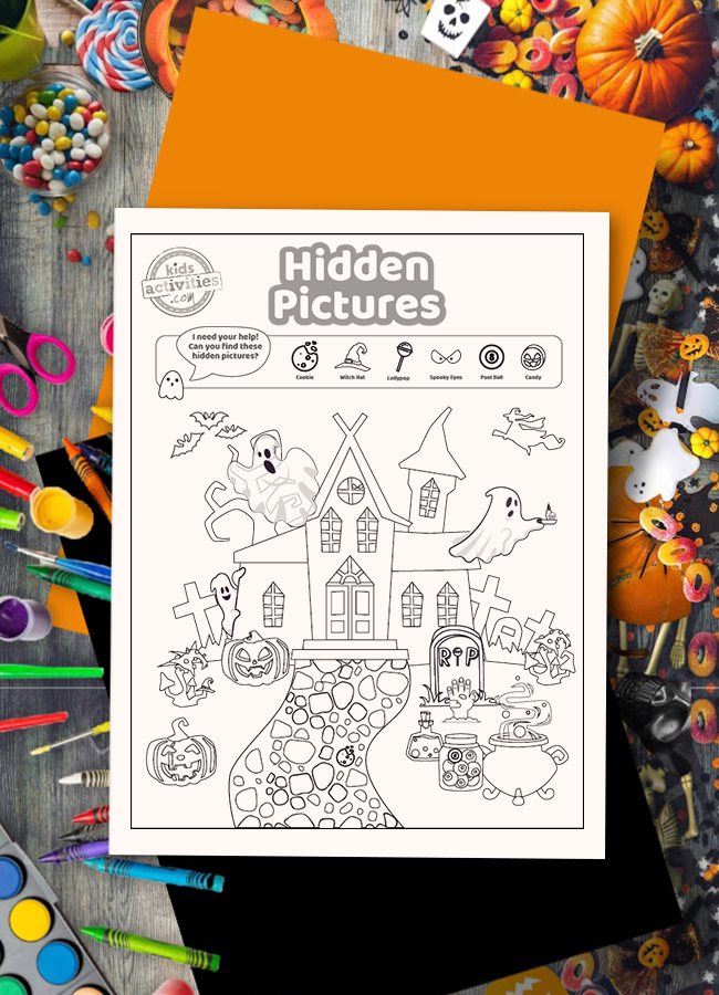 Halloween hidden picture coloring page activity on a wood surface surrounded by trick or treat candy and Halloween arts and craft supplies
