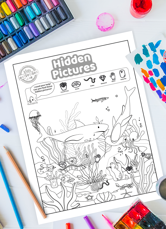 Puzzles for kids - hidden pictures shark worksheet surrounded by paint, colored pencils and other art supplies