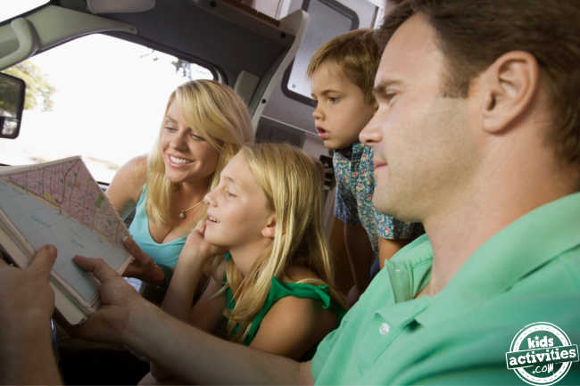 Family learning maps road games before starting their road trip in RV