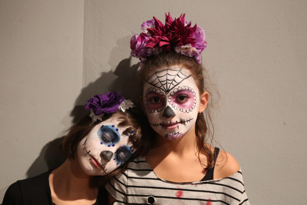 Girls with face makeup for Halloween, should Halloween change its date?