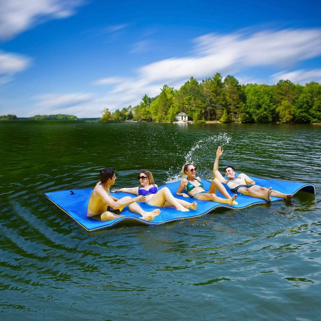 2 men and 2 women are having a blast on the 9ft floating pad on the lake.