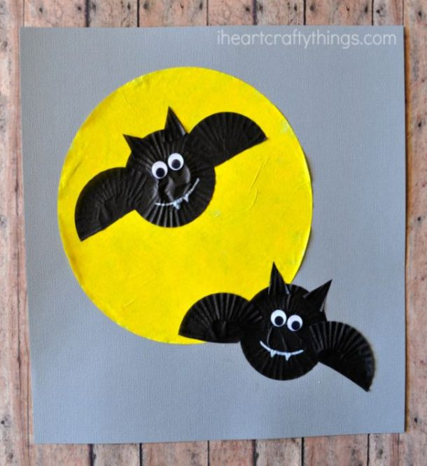Bat crafts made from cupcake liners and are set against a yellow moon on a gray piece of paper