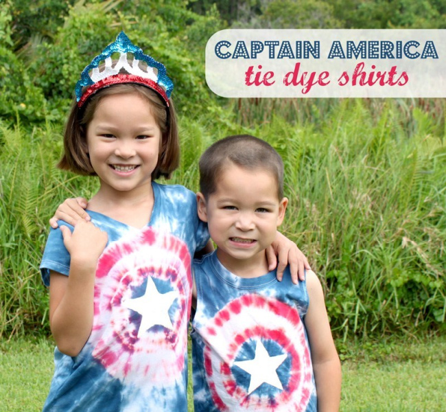 Little girl and little boy together in Captain America tie-dye shirts in front of grass.