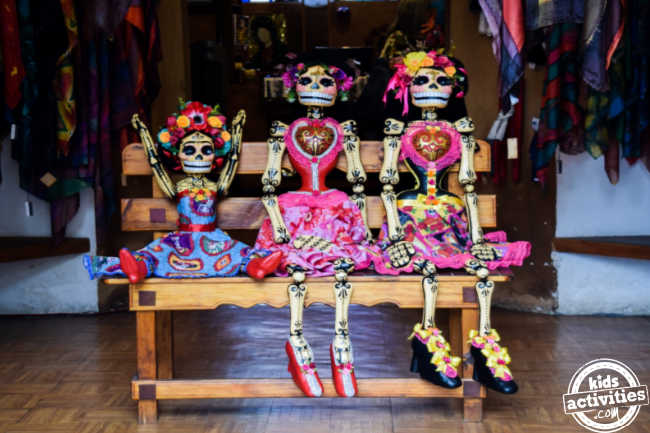 family picture of three skeletons dressed in day of the dead traditions sitting on a bench inside of a closet