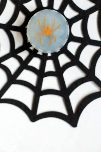 A black felt spiderweb with a bar of glycerin soap containing an orange spider inside.